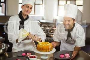 Portrait of two chefs preparing a cake