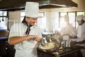 Smiling chef mixing dough