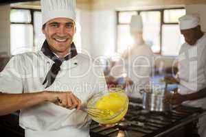 Portrait of smiling chef mixing dough