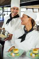 Close-up of chefs smiling while working in kitchen