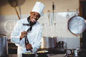 Portrait of chef sprinkling pepper on a meal