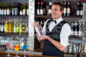 Bartender mixing a cocktail drink in cocktail shaker