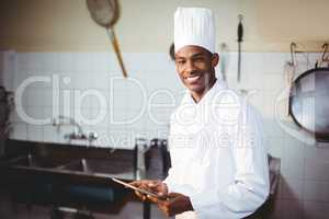 Portrait of smiling chef using digital tablet