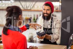 Seller taking payment with bank card reader and smartphone