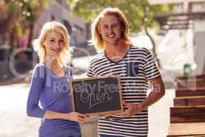Two merchants holding a board written open