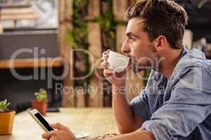 Profile view of hipster man using tablet at cafe