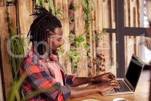 Profile of hipster man using laptop
