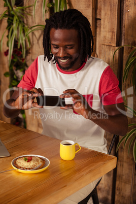 Casual man taking picture of pastry and cup of coffee