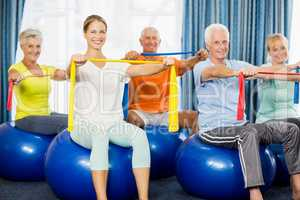 Seniors using exercise ball and stretching bands