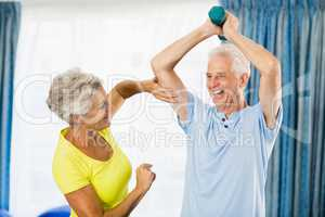 Senior woman feeling muscles of man