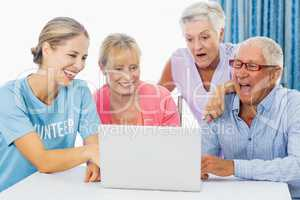Volunteer and seniors using a laptop