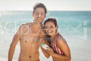 Young couple with sunscreen lotion on beach