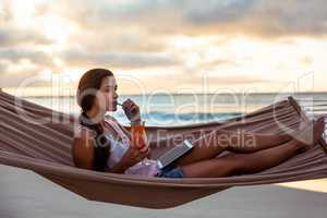 Woman having mocktail while relaxing on a hammock