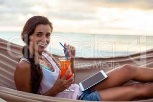 Portrait of woman holding mocktail while relaxing on a hammock