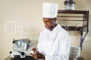 Chef making notes on a clipboard