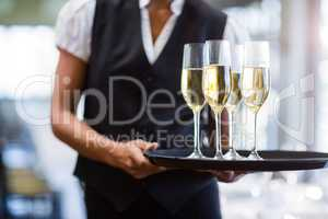 Waitress holding serving tray with champagne flutes�