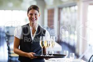Portrait of waitress holding serving tray with champagne flutes�