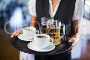 Mid section of waitress holding serving tray with coffee cup and pint of beer