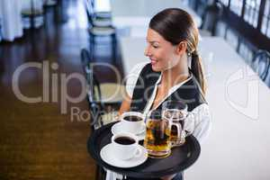 Waitress holding serving tray with coffee cup and pint of beer