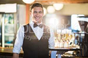 Portrait of waiter holding serving tray with champagne flutes�