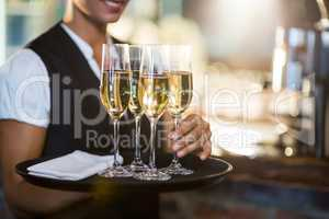 Mid section of waitress holding serving tray with champagne flutes