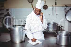Chef writing on clipboard while talking on phone