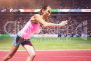 Composite image of an athletic woman starting to run