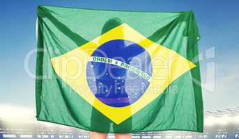 Composite image of athlete posing with brazilian flag after vict