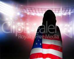 Composite image of rear view of sporty woman holding an american