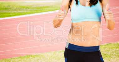 Composite image of portrait of sporty woman smiling with thumbs