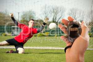 Composite image of coach is holding a stopwatch against goalkeep