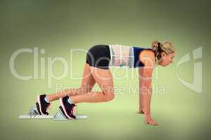 Composite image of female athlete on starting blocks
