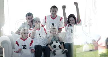 Composite image of happy family watching a football match in tel
