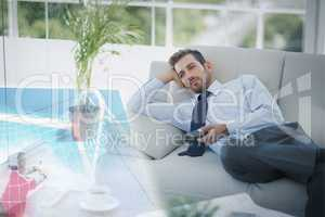 Composite image of businessman is watching sport on television
