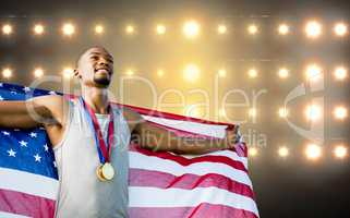 Portrait of happy sportsman posing with an american flag  agains