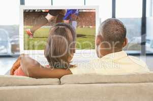 Composite image of over shoulder view of casual couple watching