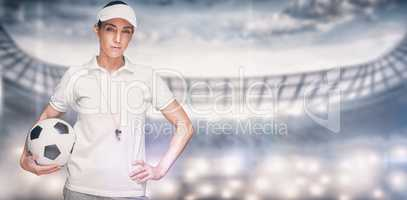 Composite image of female athlete holding a soccer ball
