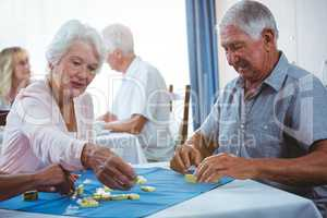 Senior persons enjoy playing domino