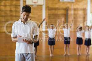 Sports teacher writing notes on clipboard while students exercis