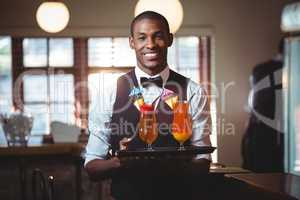 Bartender holding serving tray with two glass of cocktail
