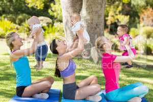 Women holding their babies while exercising