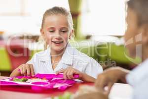 Schoolgirl having lunch during break time in school cafeteria