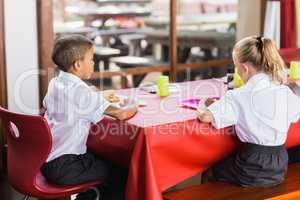 Boy and girl in school uniforms having lunch in school cafeteria