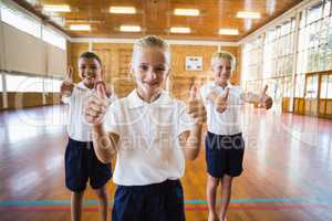 Smiling students showing thumbs up in school gym