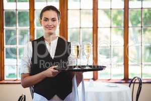 Portrait of waitress holding serving tray with champagne flutes&