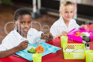 Boy and girl in school uniforms having lunch in school cafeteria