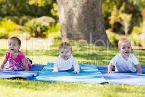 Three babies crawling on exercise-mat