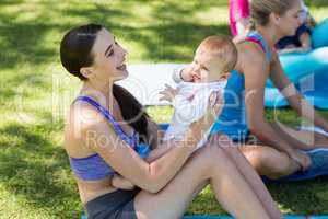 Women holding her baby while exercising