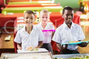 Student holding food tray in school cafeteria