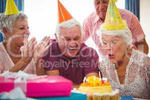 Senior woman blow on birthday cake